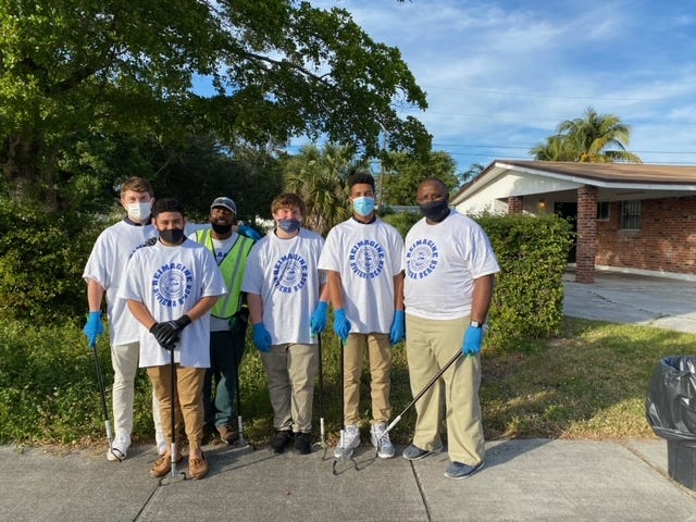 From left to right, Dwyer football players Caden Ingram and Erick Rodriguez, coach McKinley Rolle, players Declan Ingram and Preston Wade and director of football operations Ray Gordon spent Martin Luther King Jr. Day cleaning up Riviera Beach neighborhoods.