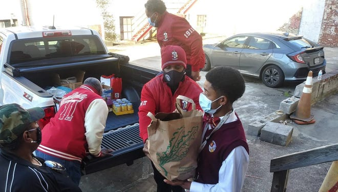 """Petersburg Councilman and Kappa Alpha Psi Fraternity, Inc. member Darrin Hill hands Petersburg Kappa League President Cornell """"Trey"""" Prince III a bag of canned goods to carry into The Hope Center in Petersburg, Va. on January 18, 2021."""
