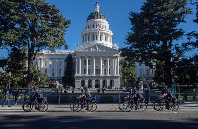 A Sacramento police bike patrol rides in front of the California State Capitol in downtown Sacramento on Monday.