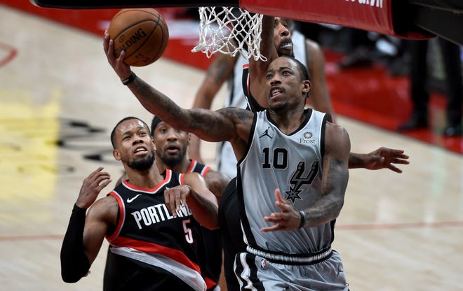 San Antonio's DeMar DeRozan (10) drives to the basket against Portland's Rodney Hood during the second half of the Spurs' 125-104 win over the Trail Blazers on Monday.