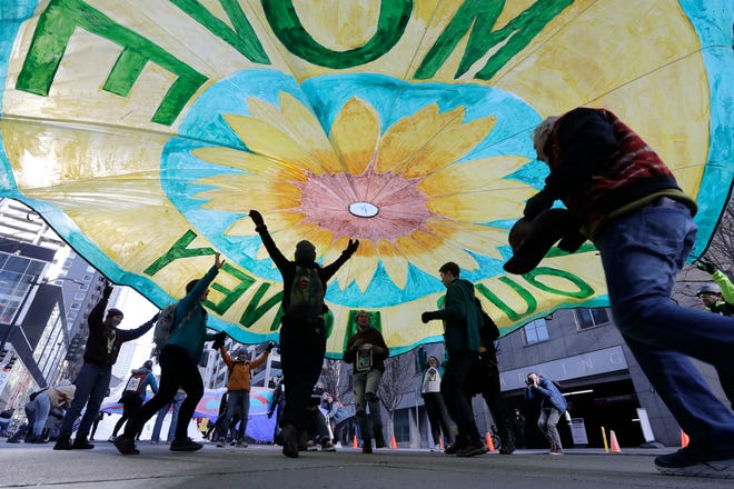 Activists run beneath a parachute-type banner as they join some 200 others to block a downtown street in protest of Chase bank funding of fossil fuel companies Wednesday, Feb. 19, 2020, in Seattle. Demonstrators, including Native Americans and First Nation drummers, raised several large tripods with protesters seated atop and held large banners to stop traffic.