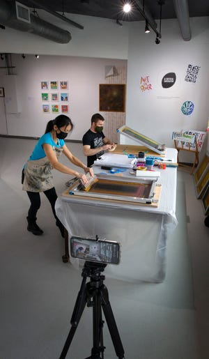 "Printmaker Mika Aono, left, and volunteer Neal Williams make silkscreen prints during a livestream at Eugene Contemporary Art's ANTI-AESTHETIC to help kick off the opening of ""A Critical Conversation,"" a multi-disciplinary project focused on the intersections of art, race and privilege at home and in culture."