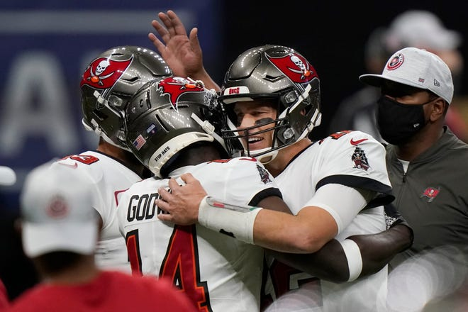 Tampa Bay Buccaneers quarterback Tom Brady (12) embraces Tampa Bay Buccaneers wide receiver Chris Godwin (14) before the first half of an NFL divisional round playoff football game between the New Orleans Saints and the Tampa Bay Buccaneers, Sunday, Jan. 17, 2021, in New Orleans. (AP Photo/Brynn Anderson)