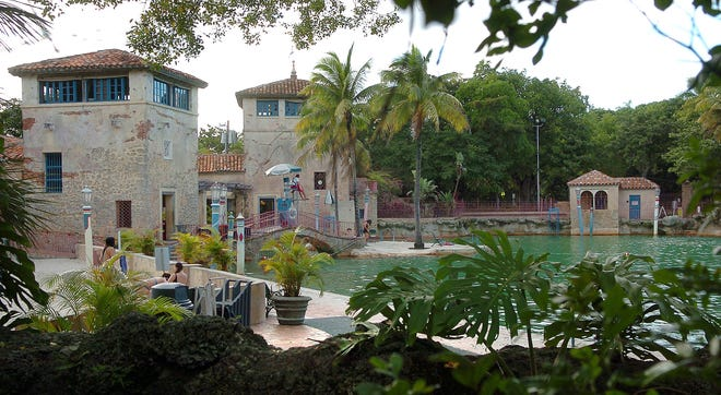 """The 800,000-gallon Venetian Pool is one of Coral Gables' many landmarks. It was built in 1923 from the original quarry from which limestone was taken for road beds and building materials for early houses in """"The City Beautiful."""" Denman Fink and Phineas Paist designed the buildings. During the boom, a wooden deck was built out over the water, from which William Jennings Bryant would orate to potential home buyers as to the virtues of Florida real estate. Bryant died in 1925, a few months before the boom went bust. (Herald-Tribune Staff photo / Harold Bubil; 9-16-2012)"""