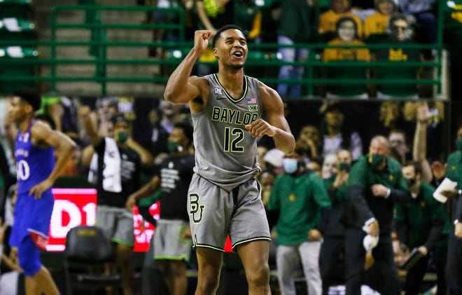Baylor's Jared Butler, front, reacts to a made basket as Kansas' Ochai Agbaji, back, turns away in the closing moments of Monday night's game at Ferrell Center in Waco, Texas. Butler scored 30 points and the No. 2-ranked Bears defeated the No. 9 Jayhawks 77-69.
