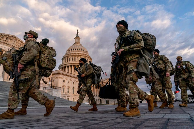 Armed National Guard troops walk past the U.S. Capitol on Jan. 18 in advance of the 59th Presidential Inauguration.