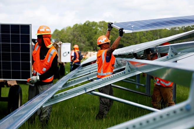 A contractor installs a panel at a solar power plant.