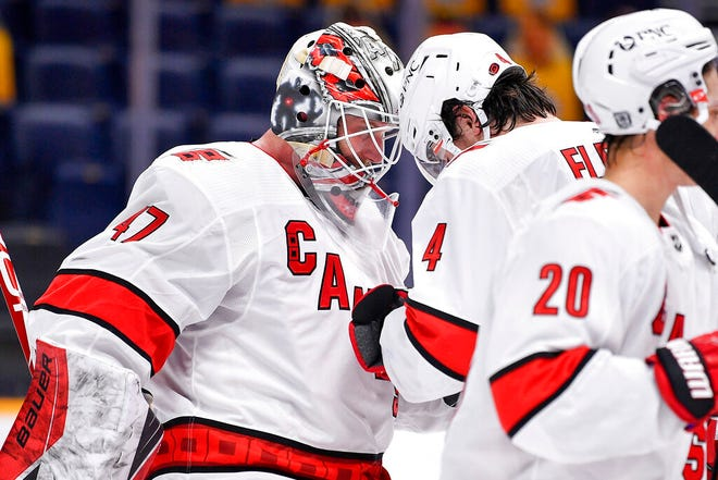 Carolina Hurricanes goaltender James Reimer (47) celebrates defeating the Nashville Predators 4-2 with defenseman Haydn Fleury (4) after an NHL hockey game in Nashville, Tenn., Monday, Jan. 18, 2021. (Andrew Nelles/The Tennessean via AP)