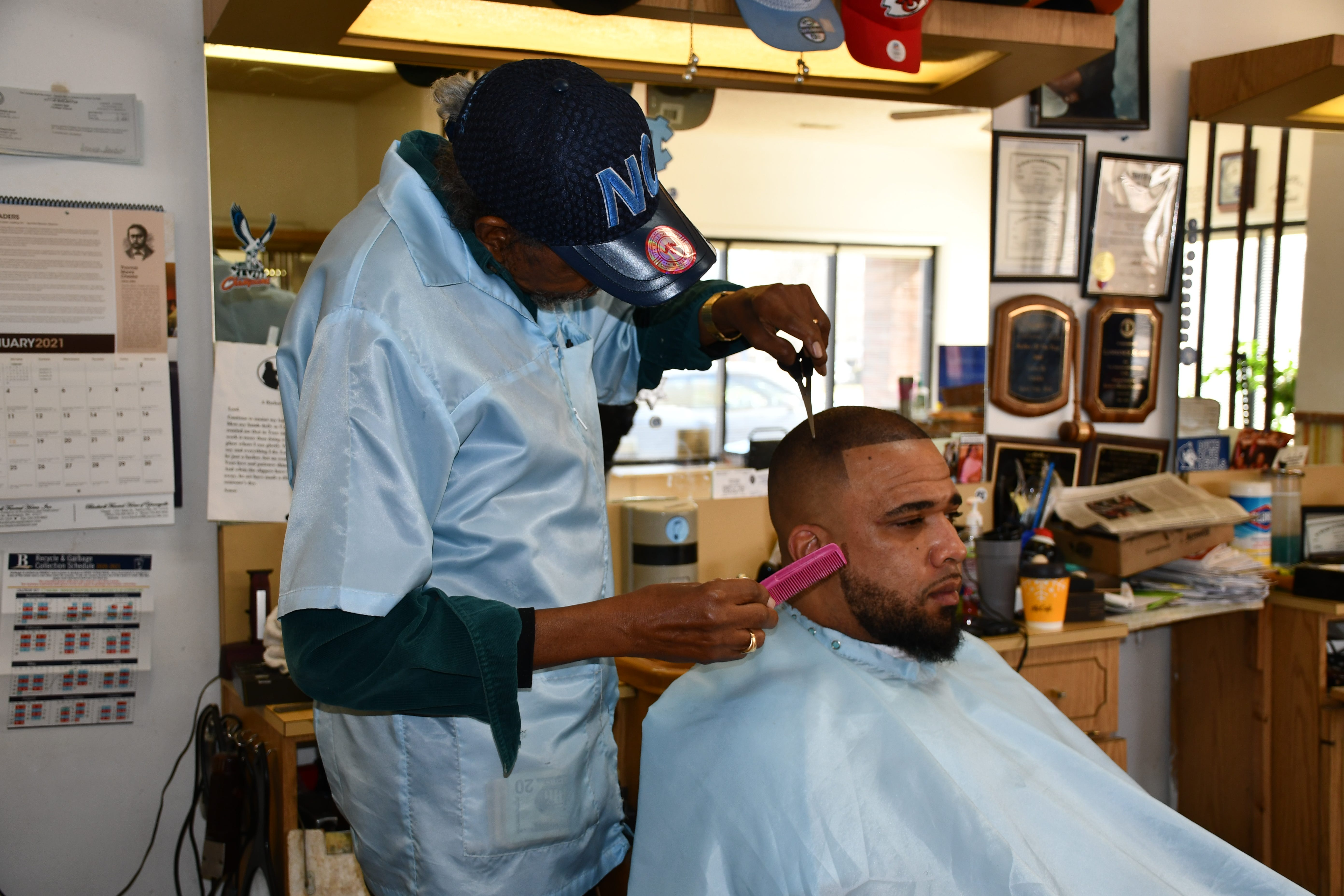 Owner Lawrence Slade puts the final touches on David Cummings' haircut inside the L&M Barbershop.