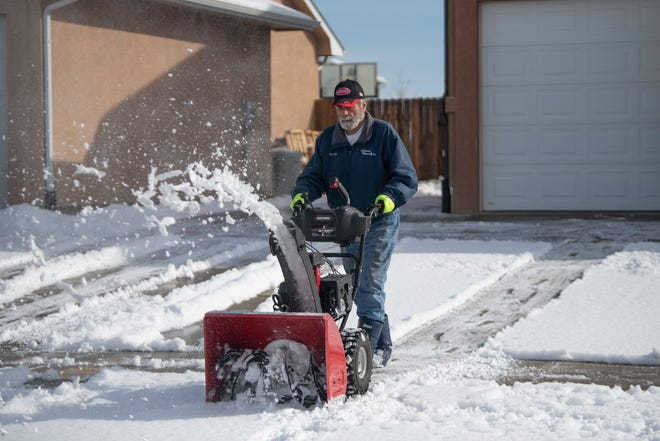 Bob Neumeister uses a snow blower to clear the driveway of his South Side home on Tuesday.