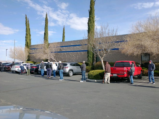 People wait in line to be vaccinated at a San Bernardino County-run health center in Hesperia on Tuesday, Jan. 19, 2021.