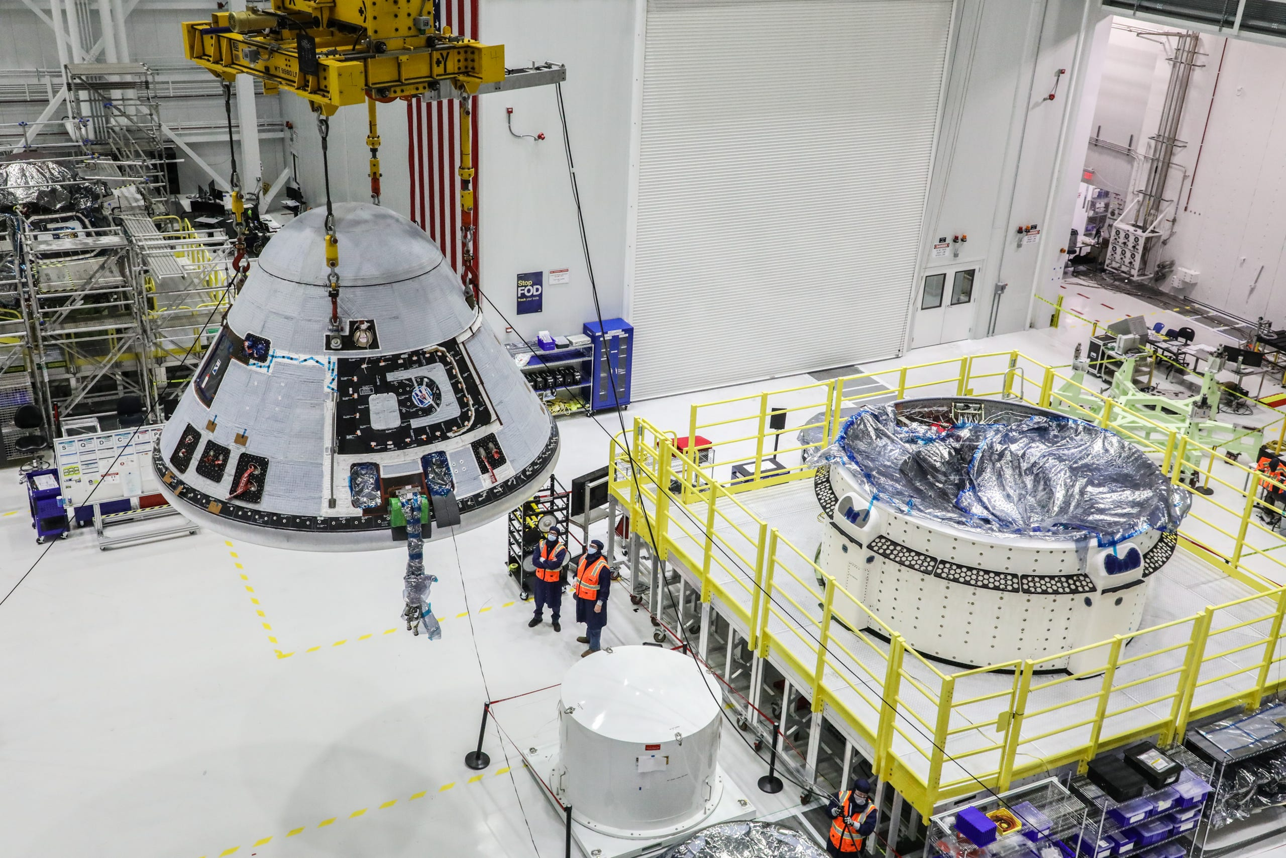 The Orbital Flight Test-2 crew module is lifted and moved in the Starliner production factory at Kennedy Space Center in Florida.