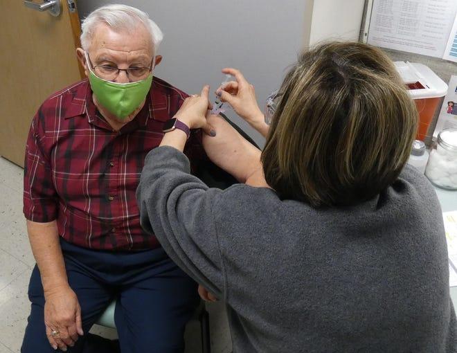 Erin Barnett, public health nurse, administers a COVID-19 vaccination to Richard Heid of Bucyrus.