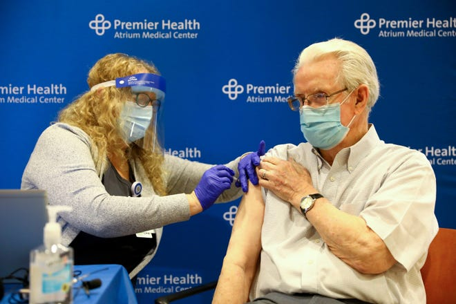 Don Pelfrey receives a dose of the COVID-19 vaccine from licensed practical nurse Tami Arnold at Atrium Medical Center in Middletown, Ohio. Some out-of-state residents are getting vaccines in Ohio and vice versa.