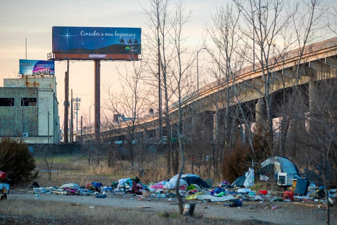 """A billboard along I-64 looms over a homeless camp along the Ohio River. """"I wish whoever paid for that billboard would have used that money to provide meaningful help to these people,"""" Feed Louisville's Donny Greene said. Jan. 14, 2021"""