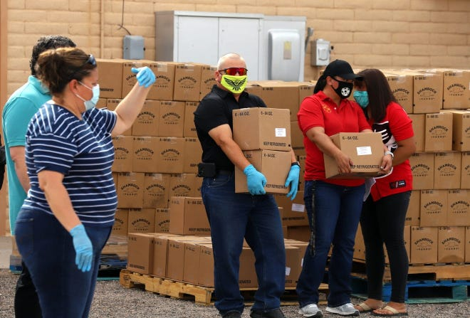 At center is Deming Cesar Chavez Charter High School Director Noel Nunez carrying food boxes among volunteers from Colores United and others.