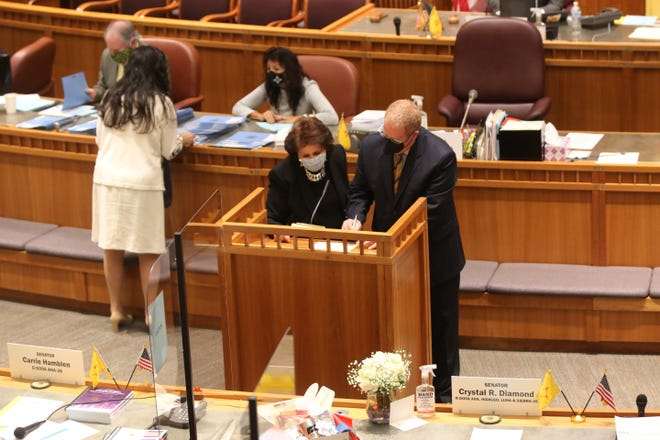 New Mexico Sen. Jeff Steinborn, D-Las Cruces, right, signs the Senate roster on the opening day of the 2021 state legislature on Tuesday Jan. 19, 2021.