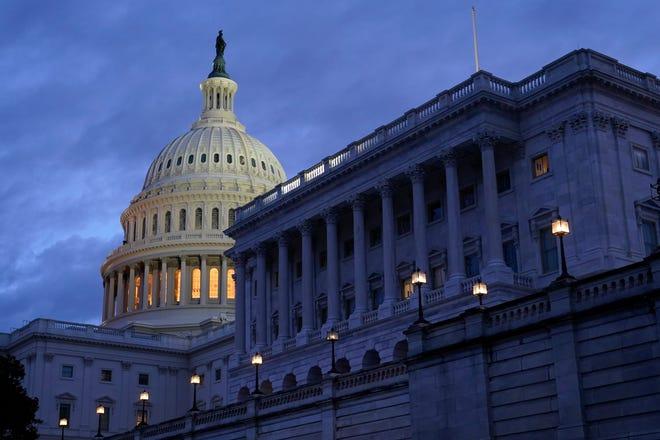 Sunlight shines on the U.S. Capitol shortly before sunrise Monday, Jan. 18, 2021.