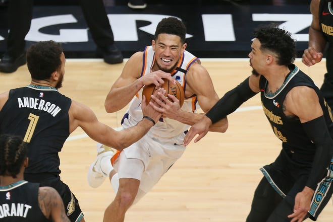 Jan 18, 2021; Memphis, Tennessee, USA; Phoenix Suns guard Devin Booker (middle) dribbles between Memphis Grizzlies forward Kyle Anderson (1) and guard Dillon Brooks (24) in the first quarter at FedExForum. Mandatory Credit: Nelson Chenault-USA TODAY Sports