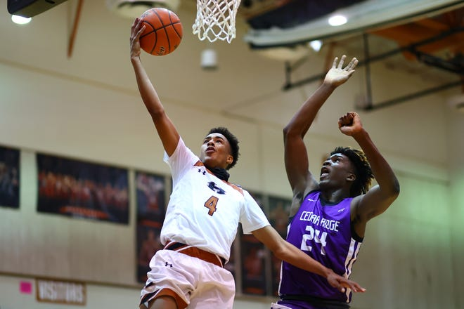 Kaden Smart soars in for layup for Hutto as Cedar Ridge's Marcel Bryant tries to block the shot during a District 25-6A game Jan. 19 at Hutto High School. Hutto defeated Cedar Ridge by a final score of 68-59 to earn a tie at the top of district standings.