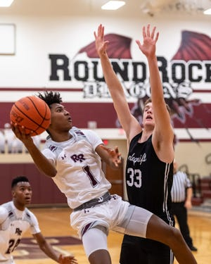 Jae'lyn Brooks puts up a shot for Round Rock against Vandegrift's Charles Morris Jan. 19 at Round Rock High School. Round Rock celebrated senior night with a 74-35 win over the defending district champions.