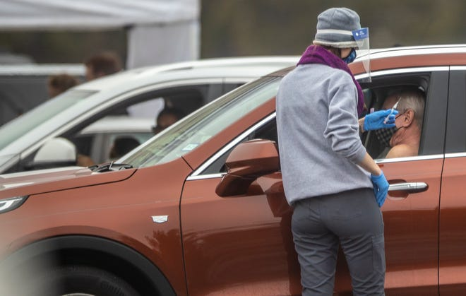 People wait in their cars as health care workers administer the COVID-19 vaccine during a drive through clinic at Kelly Reeves Athletic Complex in North Austin on Wednesday.