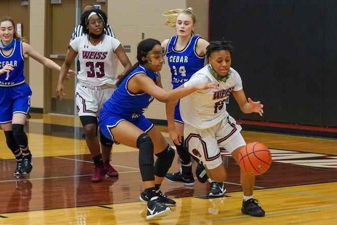 Weiss' Omareya Wash, right, steals the ball from Cedar Creek's Alexa McDonald Jan. 19 at Weiss High School. Wash had 31 points, 10 rebounds and eight steals to lead Weiss past the Eagles, 89-26