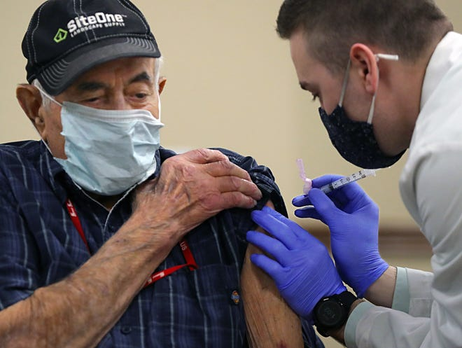 Tom Pirollo, 98, receives his first Moderna COVID-19 vaccine from pharmacist Sean Owens at the Acme Fresh Market pharmacy Wednesday in Montrose, Ohio.