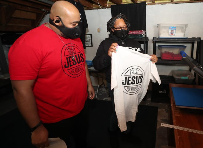Robert Greer looks at a shirt made by his wife, Bre, as the couple talk about ZaBre Inspire, a Christian apparel, photography and graphic design business they run out of the basement of their Akron home.
