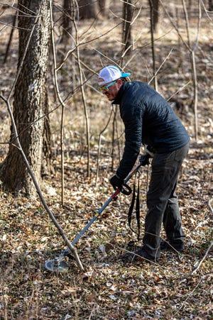 Jon Lindblom removes small shrubs from the future site of Safari Smiles Disc Golf Park on Saturday,  Jan. 16.
