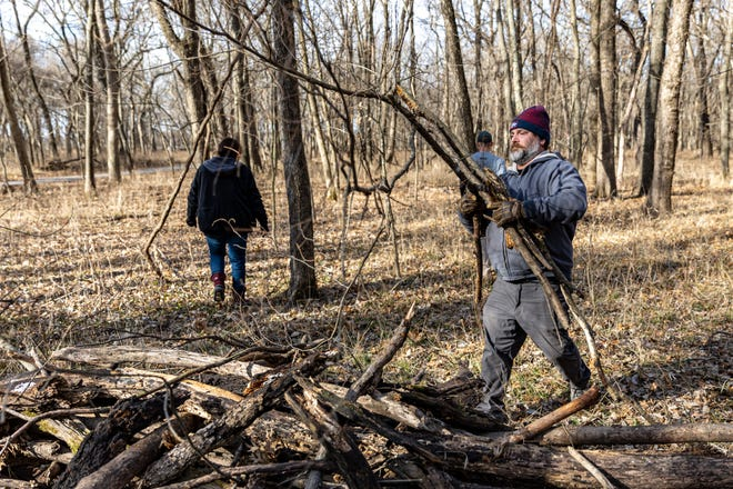 Chris Stine and other volunteers help clear limbs from the site of a new disc golf course, Safari Smiles Disc Golf Park, along the Pathfinder Parkway near by Lee Lake on Saturday,  Jan. 16. They hope to have the course ready for play this summer. The estimated cost of the project is $20,000, which is being funded fully through donations.