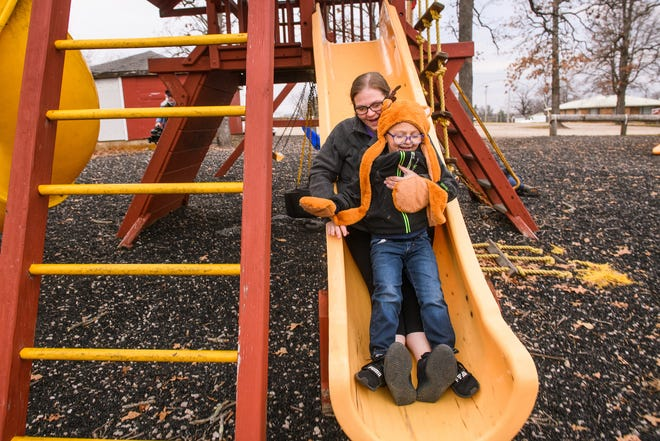 Carol Sparks-McCord goes down a slide with her son Nicholas at a park near their home in Dixon, Missouri. Sparks-McCord, a mother of three, has lost about 140 pounds since undergoing gastric bypass surgery in 2018 and can now join in the fun with her children.