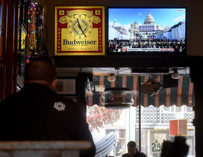 A customer at Booche's Billiard Hall watches the inauguration of President Joe Biden on television Jan. 20 as other customers wait for their orders.