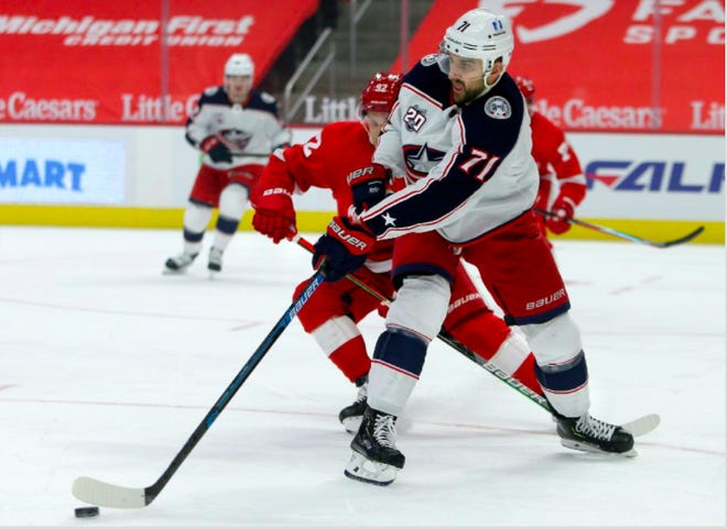 Nick Foligno (71) clears the puck against Detroit Red Wings center Vladislav Namestnikov (92) during the first period Tuesday night in Detroit. (AP Photo/Duane Burleson)