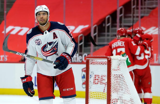 Blue Jackets defenseman Seth Jones skates away as the Red Wings celebrate Tyler Bertuzzi's goal 15 seconds into overtime on Tuesday to give Detroit a 3-2 victory.