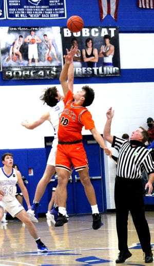 Meadowbrook senior Davis Singleton (10) and Cambridge senior Sean Perkins (4) battle on the opening tip-off Tuesday night between the Guernsey County rivals.