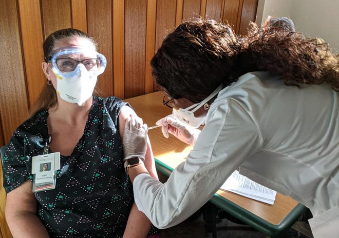Kim Schuch-Estep, the director of nursing at the Wayne County Care Center receives a COVID-19 vaccine.