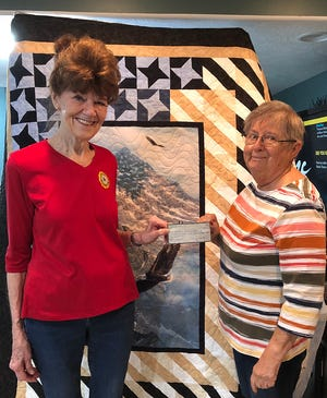 American Legion Auxiliary president Paula Sellens presents Mary Johnson with a $750 check for the Quilts of Valor organization.