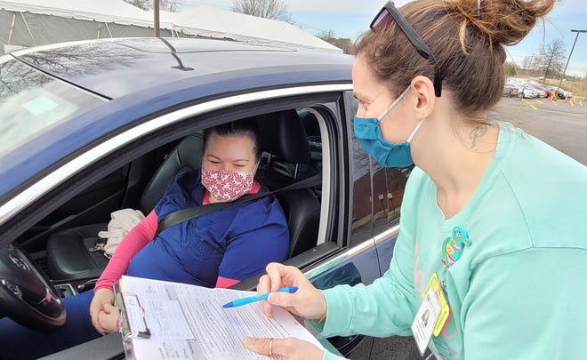 MRMC Employee Lana Compton reviews the consent form with health care worker Jennifer Fox from Spring Hill at a dive through COVID-19 vaccination center at Columbia State Community College in Columbia, Tenn. on Wednesday, Jan. 20, 2020.