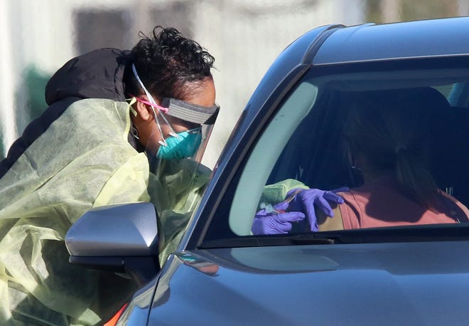 A woman gets a COVID-19 vaccine while in her car last week at the Volusia County Fairgrounds in DeLand.