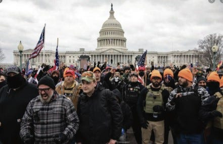 Joe Biggs, bottom left, in gray and black checked jacket, marches at the Jan. 6 riot at the U.S. Capitol, in this photo shared in a Department of Justice affidavit supporting Biggs' arrest.