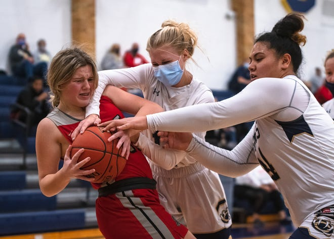 William Chrisman's Jacque David, right, and Lillian Miller, center, try to wrench the ball away from the grasp of Fort Osage's Ashlyn Buntin in Tuesday's game at Chrisman. The host Bears went on to claim a 61-21 victory.