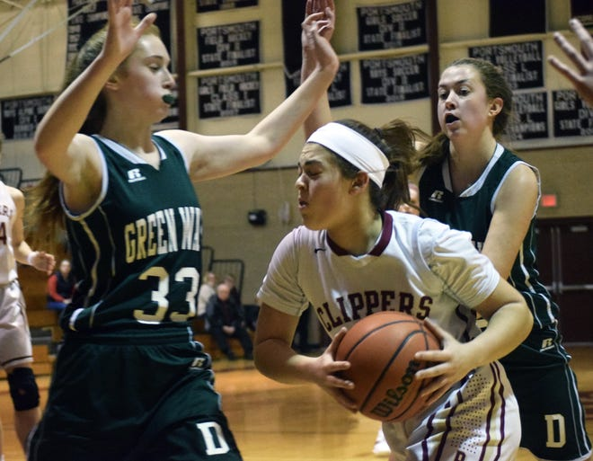 Portsmouth point guard Arianna Hebert drives against Dover defenders Morgan Raineri (33) and Sam Romps during a Division I girls basketball game in 2019. Dover's winter sports teams have been approved to play in winter 2021 amid the coronavirus pandemic.