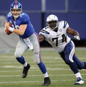 In this Nov. 8, 2009 file photo, San Diego Chargers defensive end Jacques Cesaire pursues New York Giants quarterback Eli Manning during a game in East Rutherford, N.J. Cesaire, a Gardner High alum, is in his first season as an assistant defensive line coach for the Buffalo Bills, who will meet the Kansas City Chiefs in the AFC Championship game on Sunday. (AP File Photo/Bill Kostroun)