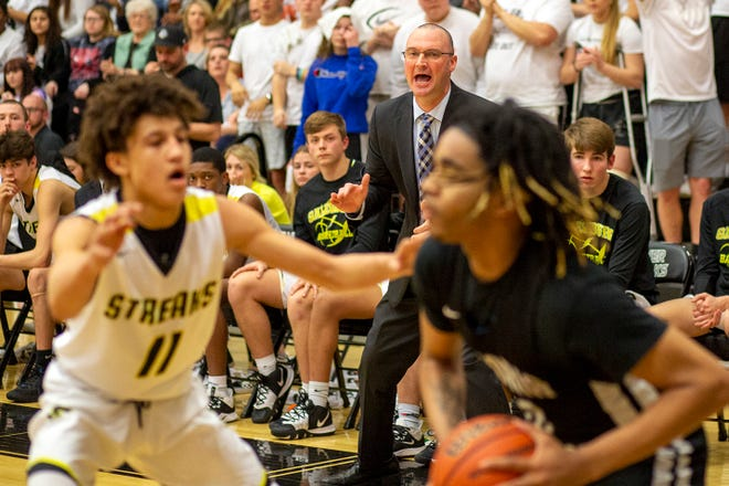 Galesburg High School boys basketball coach Ryan Hart, background, yells out instructions to his squad while the Streaks' Kyleb Meadows guards a member of the Peoria Manual Rams on Friday, March 6, 2020 in Class 3A regional championship action at John Thiel Gym.