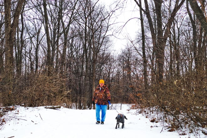 """Gary Smith of Galesburg takes his dog """"Joxer"""" for a walk on the path along North Lake Storey Rd. on Tuesday, Jan. 19, 2021. The Galesburg City Council is considering a plan that would expand Lake Storey for more recreation and housing."""