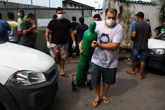 Um familiar de um paciente hospitalizado com COVID-19 espera na fila, segurando um tanque de oxigénio vazio, à espera de o reabastecer, no passado dia 15 de Janeiro de 2021, no exterior da companhia Nitron da Amazónia, em Manaus, estado do Amazonas, Brasil.