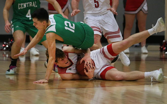 Central Christian's Adre Ibarra (12) falls over Little River's Braxton Lafferty (4) during their game at the Burrton Invitational Tournament Tuesday night. Little River defeated Central Christian 57-49.