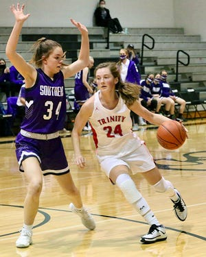 Trinity Catholic's Hayley Hughes (24) drives past Southeast of Saline's Reagan Goetz (34) during their game Tuesday at the Sterling Invitational Tournament. Southeast of Saline defeated Trinity 57-42.