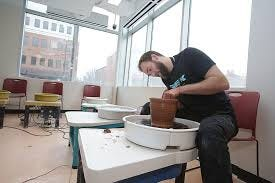 Tyler Lutz, manager of the ceramics studio in the Massillon Museum, creates a vase on a pottery wheel in the studio, which opened last year.